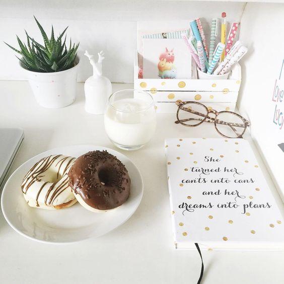 Escrivaninha com itens brancos, um journal branco com bolinhas douradas, óculos, uma suculenta, canetas coloridas, cartões de coelho e um como de leite com dois doughnuts deliciosos.: