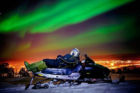 Reclining on a snowmobile, a sky-watcher in Karasjok, Norway, basks in the glow of the northern lights on February 20, 2012.