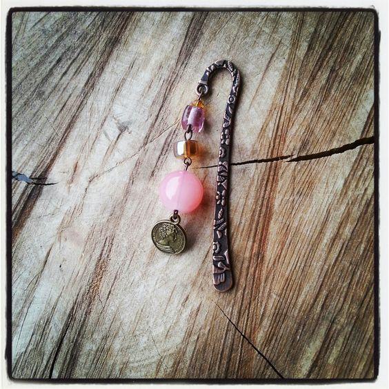 Mini boekenlegger munt,  Kleine boekenlegger van ongeveer 8cm. Er hangen glaskralen aan in de kleuren roze en topaas. Onderaan hangt een bronskleurig muntje.  De pin steekt u tussen de bladzijde en de kralen hangen buiten het boek.