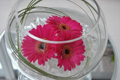 Glass fish bowl centerpiece with clear gel, 3x pink gerberas and bear grass on a round mirror plate. Very simple but effect. Also looks nice with little tea lights around mirror or crystals scattered around.
