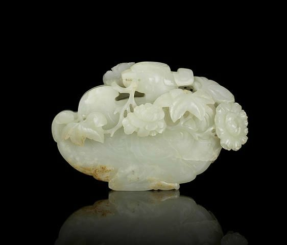 A rare pale green jade carving of a Mandarin duck and peony blossoms, Qianlong period (1736-1795 AD).