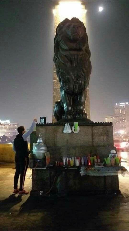 القبح أصبح عادة وهواية الإستسهال نتيجة التجاهل والإهمال بائع يفرش أمام أسد كوبرى قصر النيل ويرص بجوار الأسد شخص بجح وإهمال Image Statue Buddha Statue