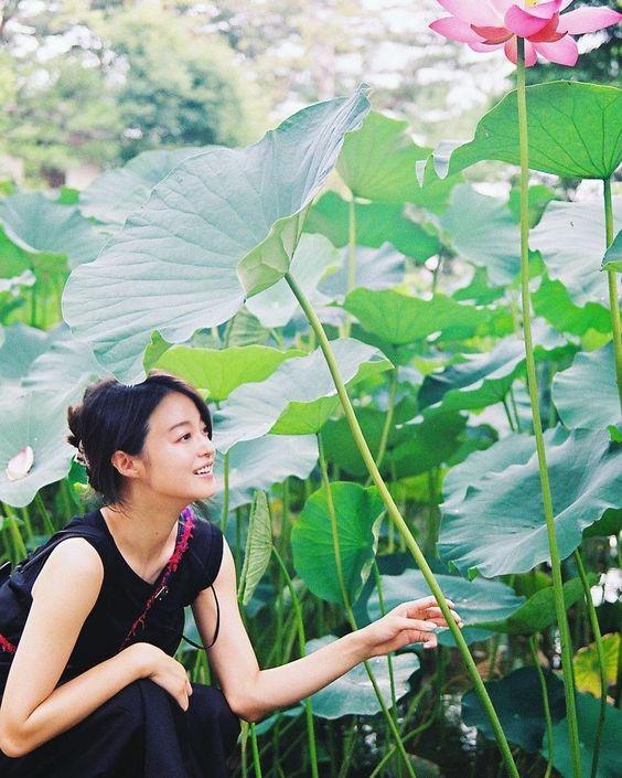 大きな蓮の花の元に座っている小林涼子の画像