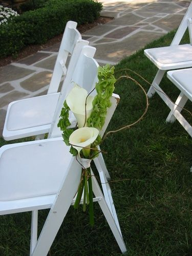 Wedding Flowers - Contemporary yet natural chair flower decoration of calla lilies, bells of ireland and a touch of grapevine.