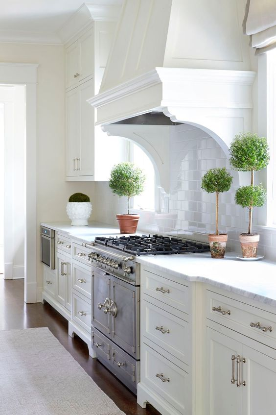 White kitchen with traditional style and topiaries. Sarah Bartholomew Traditional Colorful Decor. #whitekitchen #classic #topiary