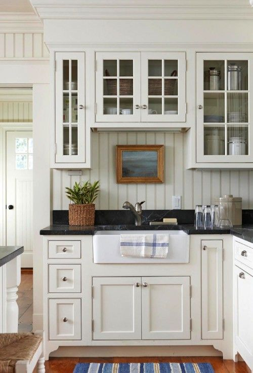 kitchen with white cabinets and black marble countertops-love the beadboard basksplash