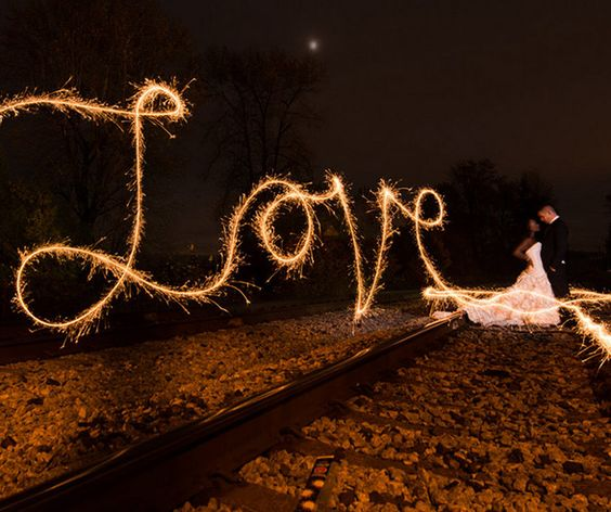 "A couple is illuminated by the warm amber glow that beams from the word ""Love"" written using sparklers."