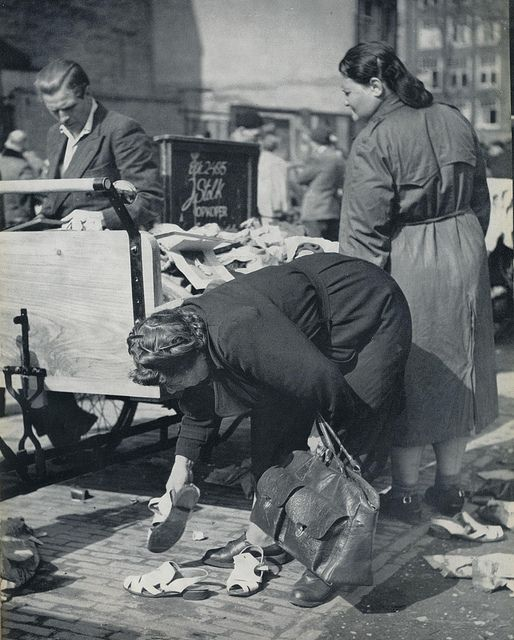 1957. Looking for second-hand shoes at the Waterlooplein flea market in Amsterdam. Photo Kees Scherer. #amsterdam #1967 #waterlooplein
