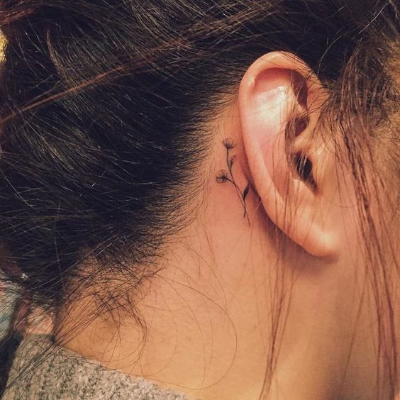 tiny flowers tattoo behind the ear: