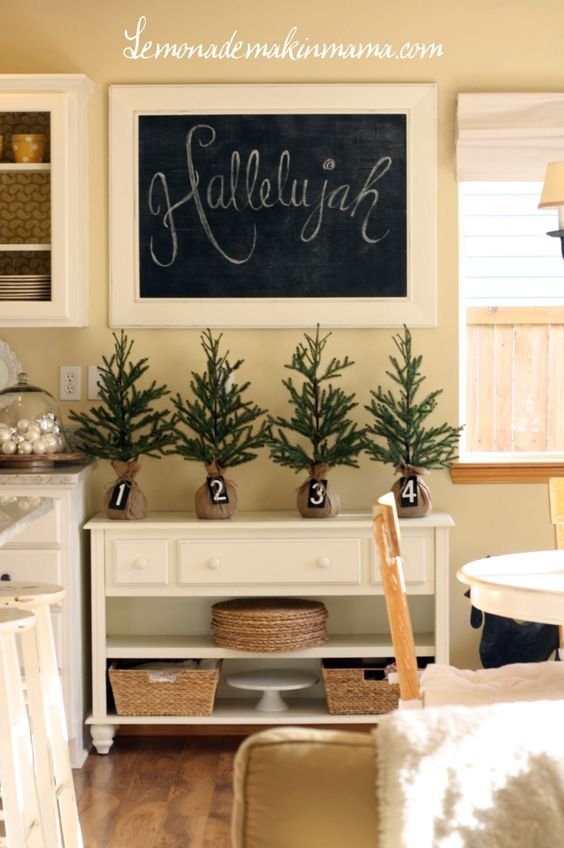 Simple + sweet holiday decorating. I love the burlap wrapped trees and simple chalkboard message.