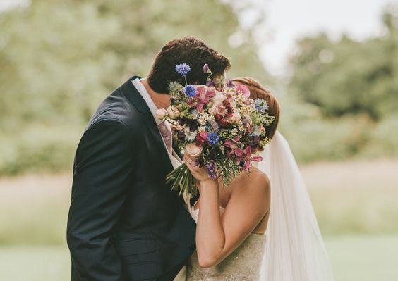 Bright rustic hand tied bridal bouquet for Clock Barn bride created by Eden Blooms Florist.  Made from Tanacetum Daisy, Sweet Pea, Pink Astrantia, Oregano, Cornflower, Nigella, Alchimilla, Mint, Rosemary & Bombastic Spray Rose. Image by www.tomhalliday.com