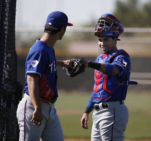 Texas Rangers pitcher Yu Darvish speaks with catcher Robinson Chirinos after Darvish threw in a live batting practice during a workout at the Rangers spring training facility in Surprise, Arizona Wednesday February 25, 2015. (Andy Jacobsohn/The Dallas Morning News)