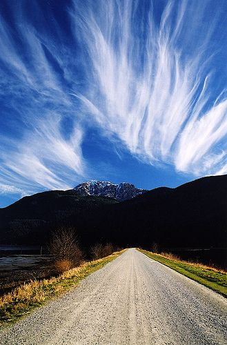 Long dirt roads, mountains and clouds