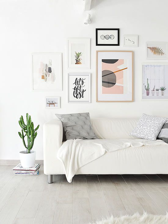Color palette is key in Scandinavian style and typically includes just one or two pale accent colors paired with a white foundation. Hints of black are often added for dimension, but otherwise keep your own Scandinavian-inspired space sparsely colored, like this living room that gains pale pink color through its geometric gallery wall./