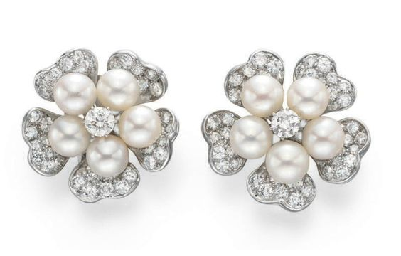 A PAIR OF DIAMOND AND CULTURED PEARL EAR CLIPS, BY VAN CLEEF & ARPELS  Each designed as a flower, centering upon a circular-cut diamond pistil, within a cultured pearl surround, extending circular-cut diamond sculpted petals, mounted in platinum, in a Van Cleef & Arpels blue suede pouch