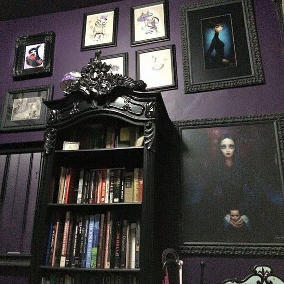 gorgeous gothic style bookshelf against a purple (eggplant) wall and miss matched picture frames