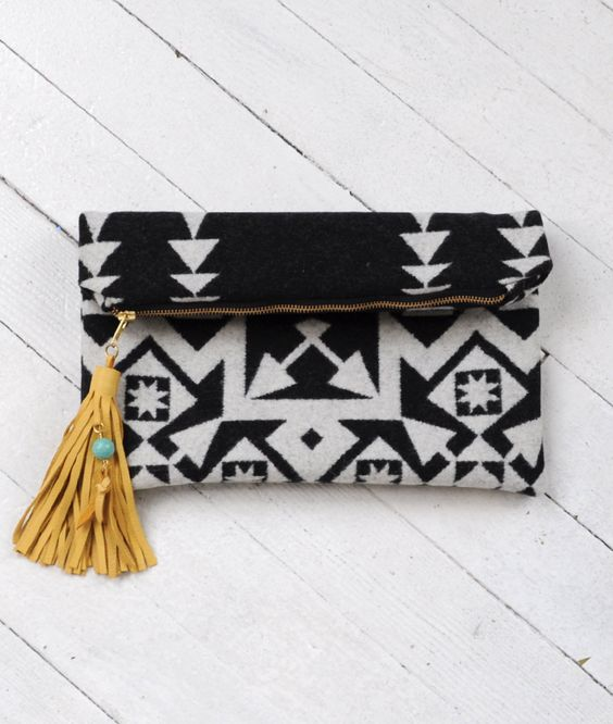 """Nighthawk ClutchDesigner: s e a e c h o$68.00 Striking jacquard clutch crafted from virgin Pendleton wool made exclusively for Summerland by s e a e c h o. Features a thick leather tassel with turquoise bead detail and sturdy canvas lining. Measures 14"""" x 12"""" and 14"""" x 9"""" when folded. The perfect size to hold all the essentials with easy transition from day to night."""