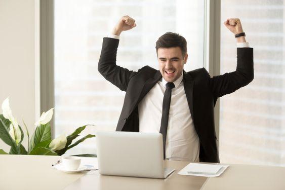 Hombre celebrando frente a una laptop (imagen digital)