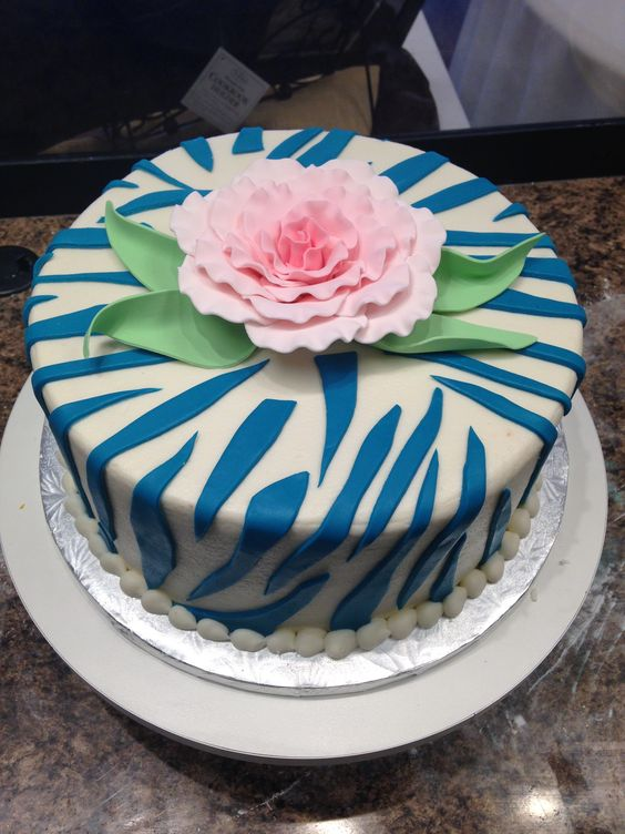 Blue zebra stripes with a pretty pink flower on top.