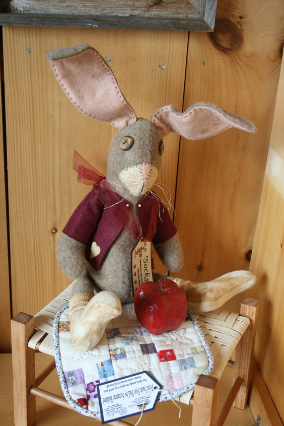 "Chris Hilliard's ""Socks"" the rabbit on a feed sack fabric mat by Suzanne Bullard on a Kellie Vance footstool"