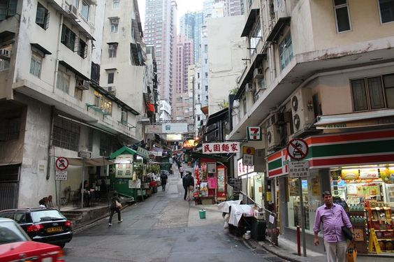Chine Hong Kong - The old vs. the new Photo by Jessica Phillips — National Geographic Your Shot - Skyscrapers can be seen from a narrow street lined with small shops in Hong Kong.