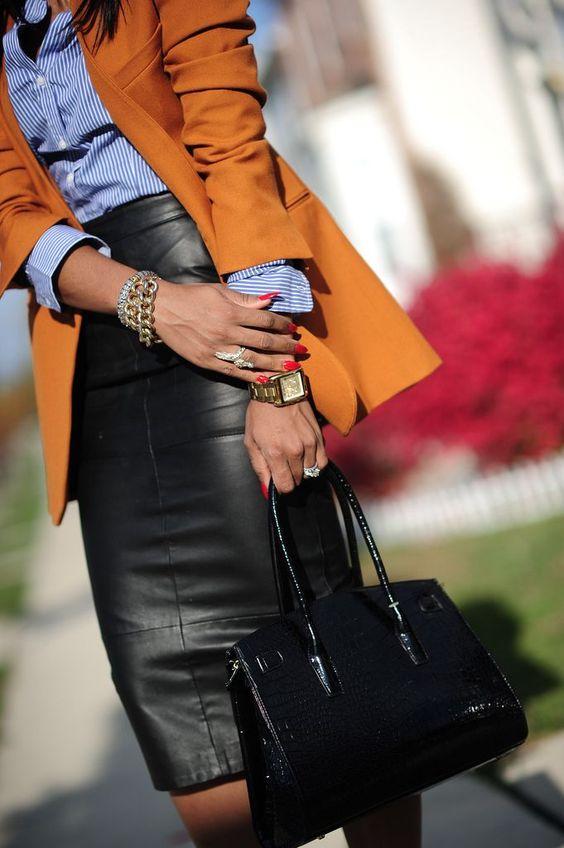 Falda midi de tubo, de cuero, color negro. Camisa de rayas blancas y azul añil, con mangas largas, metida dentro de la falda. Americana oversize, color naranja. Bolso negro.
