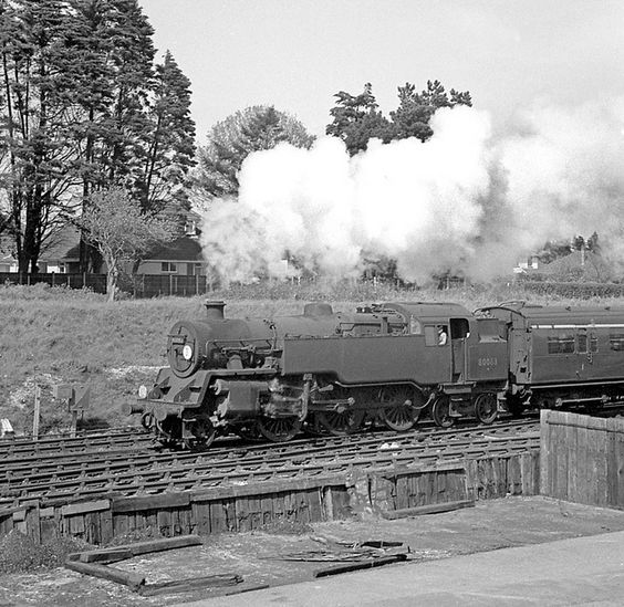 A BR Class 4 tank pulls out of New Milton with a westbound local from Eastleigh to Bournemouth. Negative scan. Hampshire, UK.