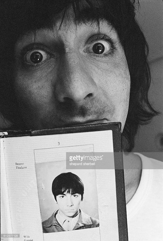 The Who's drummer Keith Moon holding an older photograph of himself on a UK passport.