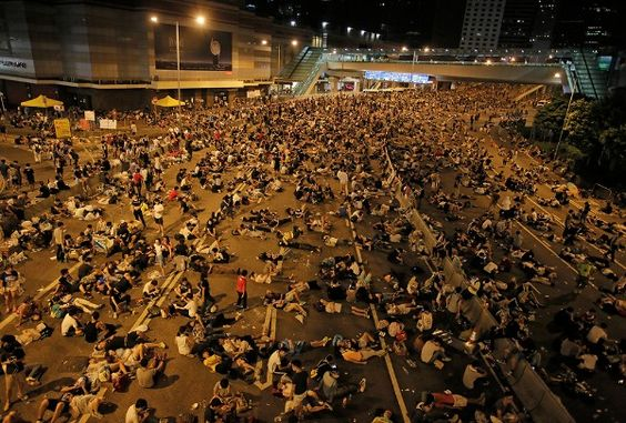 SIT-DOWN STRIKE Protesters take rest at a main road in the financial central district after riot police use tear gas against them as thousands of people blocked the road in Hong Kong, Sunday, Sept. 28, 2014. Hong Kong police used tear gas on Sunday and warned of further measures as they tried to clear thousands of pro-democracy protesters gathered outside government headquarters in a challenge to Beijing over its decision to restrict democratic reforms for the city.