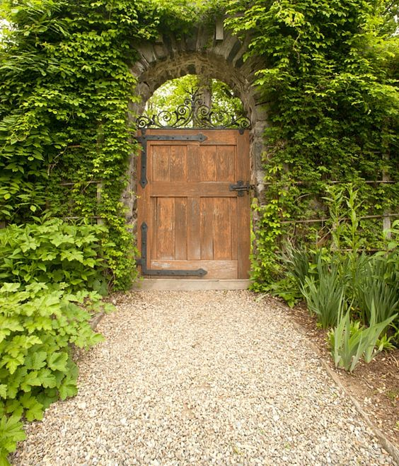 Garden gate ideas and inspiration: a rustic wood garden gate door with iron straps on a gravel path in a lush secret garden. #gardengate #secretgarden #frenchcountry #gravel