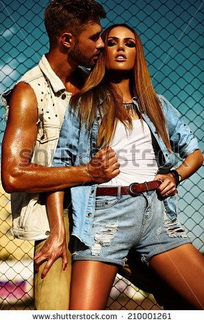 High fashion look.glamor beautiful couple sexy stylish blond young woman model with bright makeup with perfect sunbathed skin and handsome muscled man in vogue style in jeans outdoors behind blue sky: