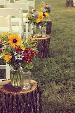 what a simple yet gorgeous touch for the end of a country style wedding aisle- tree trunk pieces used for small end tables to hold votives and flower.