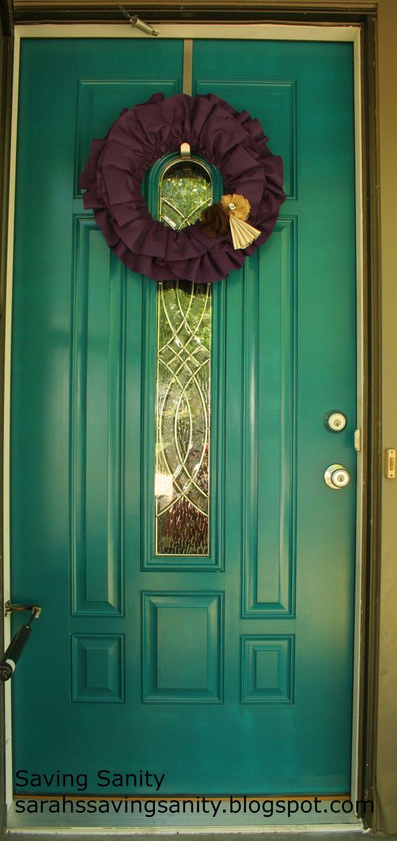 teal painted front door with a gorgeous purple wreath!!!