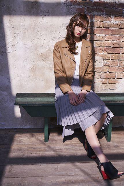 グレーのフレアスカートをはいたベンチに座る梅澤美波の画像