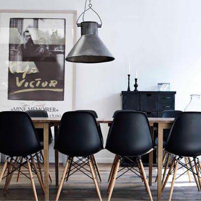Comedor que mezcla el estilo industrial con una mesa escandinava y unas bellas sillas Eames en negro.