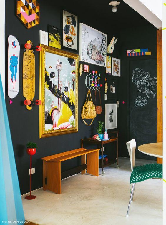 Hall de entrada tem parede pintada de tinta lousa preta e composição de quadros.