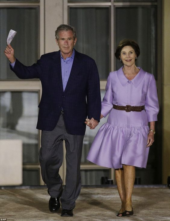Color-coordinated: Former president George W. Bush, left, and former first lady Laura Bush enter for the lighting of Freedom Hall at the George W. Bush Presidential Center in Dallas