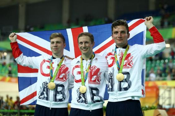Philip Hindes, Jason Kenny and Callum Skinner of Great Britain celebrate after winning gold and getting an Olympic record in the Men's Team Sprint
