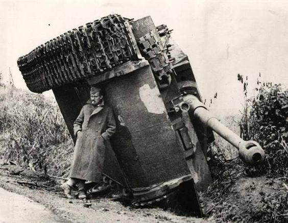A British soldier hiding from the rain under an overturned Tiger tank. Italy, 1944.