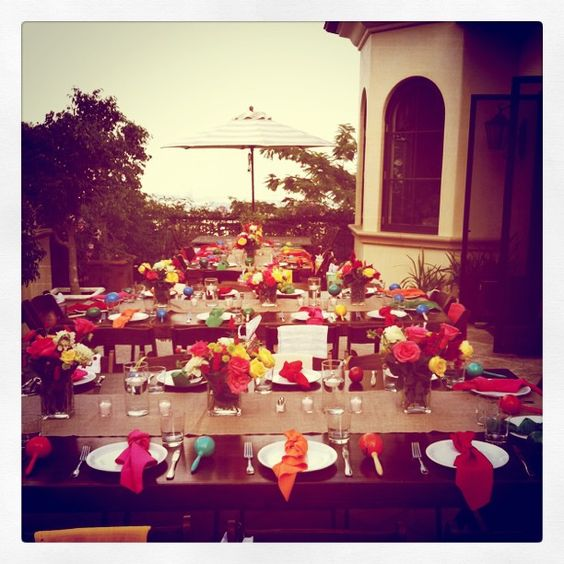 Fiesta celebration.  Wooden tables, burlap runners, multi-color napkins, colorful centerpieces with chili peppers in flowers.  #nozza