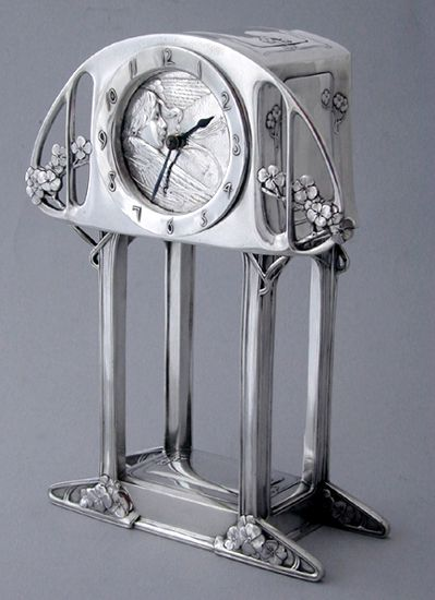 KATE HARRIS for HUTTON & SONS: An Art Nouveau silver timepiece.The clock face depicting a  Celestial Angel whose breath moves The Hands of Time.