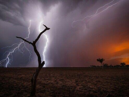Relâmpago em uma noite de tempestade perto de Port Hedland, Western Australia, inflama bushfires que enviam-se um brilho alaranjado.