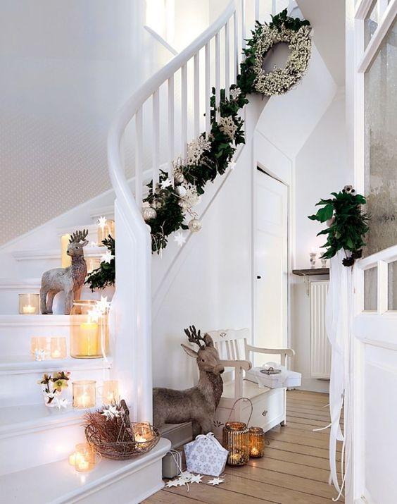 décoration de Noël intérieur - guirlande verte, boules de Noël, étoiles de couleur argent, bougies et figurines de cerfs ornent l'escalier blanc: