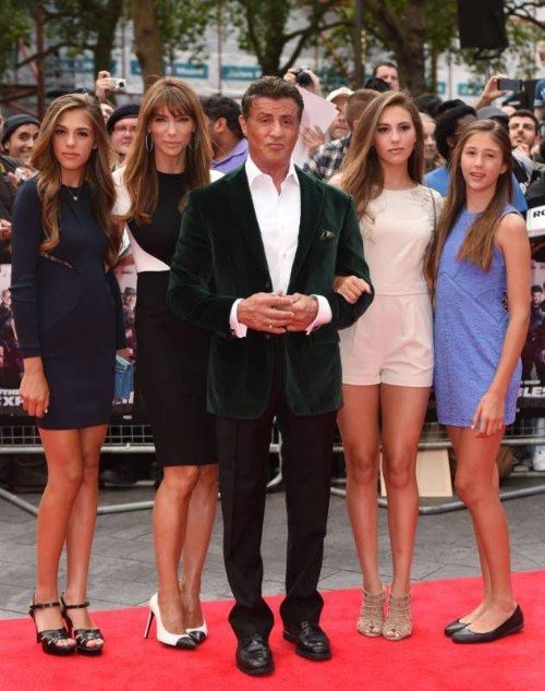 Sylvester Stallone posing on the red carpet with his compelling family, which consists exclusively of the female.