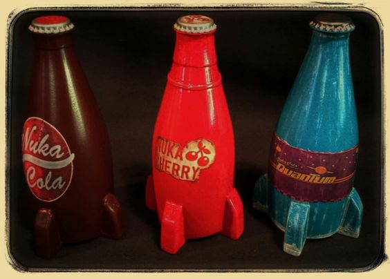 """All three of my """"poor man's"""" Nuka Cola bottles from Fallout 4. From left to right, Nuka Cola, Nuka Cherry and Nuka Cola Quantum. Made using Perrrier plastic bottles, foam core poster board, Owens Corning  foamular insulation foam, bottle caps and labels printed on regular paper that was coated in Elmers Glue-All then the whole bottle was clear coated with rustoleum clear gloss engine enamel."""