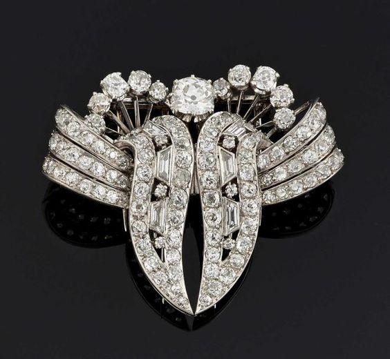BROCHE pouvant former deux clips de revers en or gris 18 k (750°/oo) et platine à décor de volutes, entièrement sertie de diamants principalement ronds, un au centre plus important de forme coussin et… - Pescheteau-Badin - 17/06/2015
