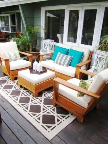 "Without the area rug, this is some patio furniture. With it, it's an outdoor living room. A few ""indoor"" details like candles and plant stands make it feel more cozy and roomlike."