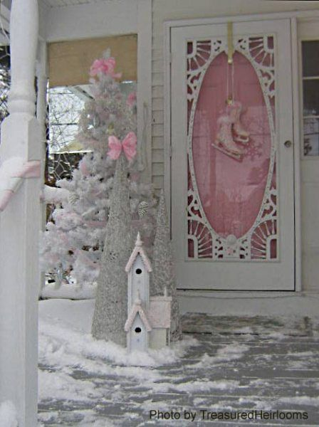 Snowy porch with Christmas decorations, pink front door, vintage screen door, ice skate decorations