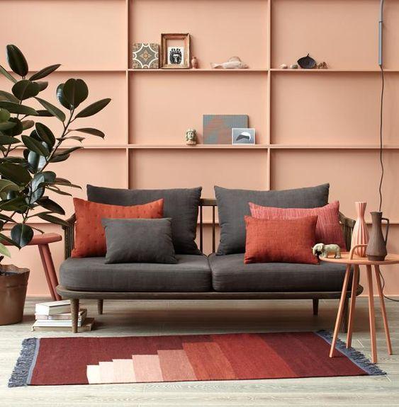 XXL-Setzkasten aus Pressspanplatten und Holzleisten hinterm Sofa. Das trägt passend zu den Teppichfransen dunkles Steingrau, das die warmen Rottöne leuchten...