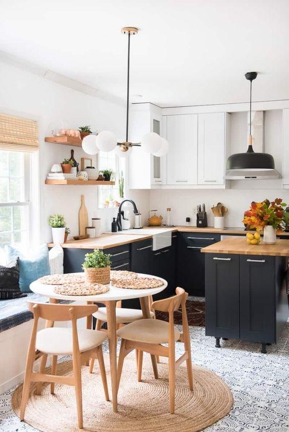 Une cuisine noire et bois très lumineuse grâce aux touches de blancs et au sol clair.